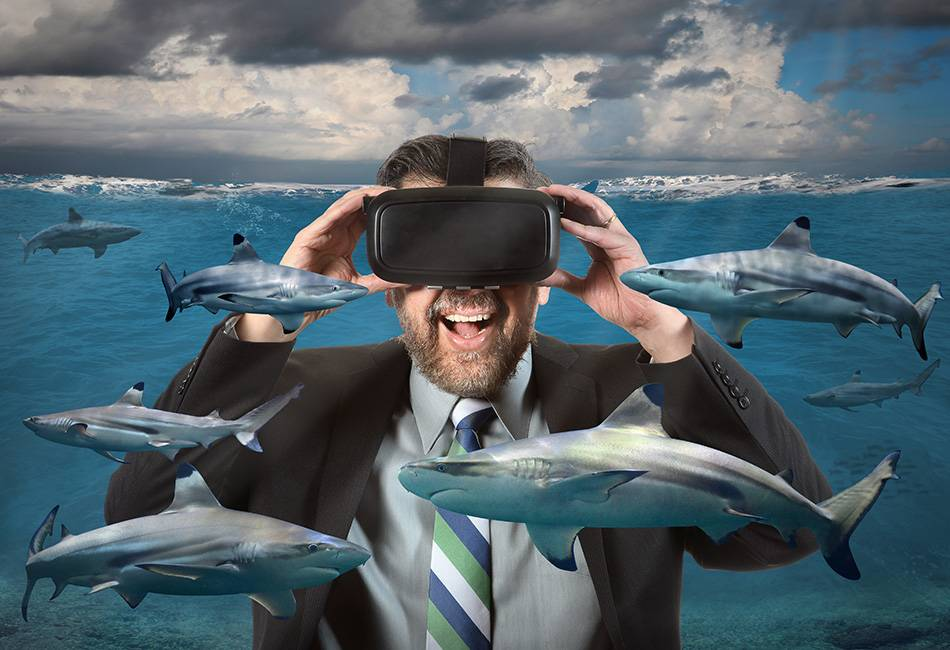 Businessman seeing sharks in the ocean using virtual reality glasses