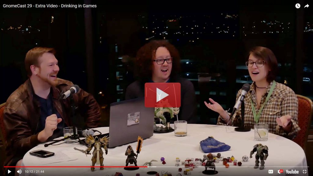 John Arcadian, Tracy Barnett, and Darcy Ross sit at a table scattered with gaming miniatures, microphones, and drinks as they talk animatedly!