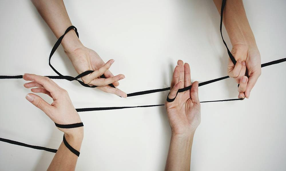 hands attached by black ribbon