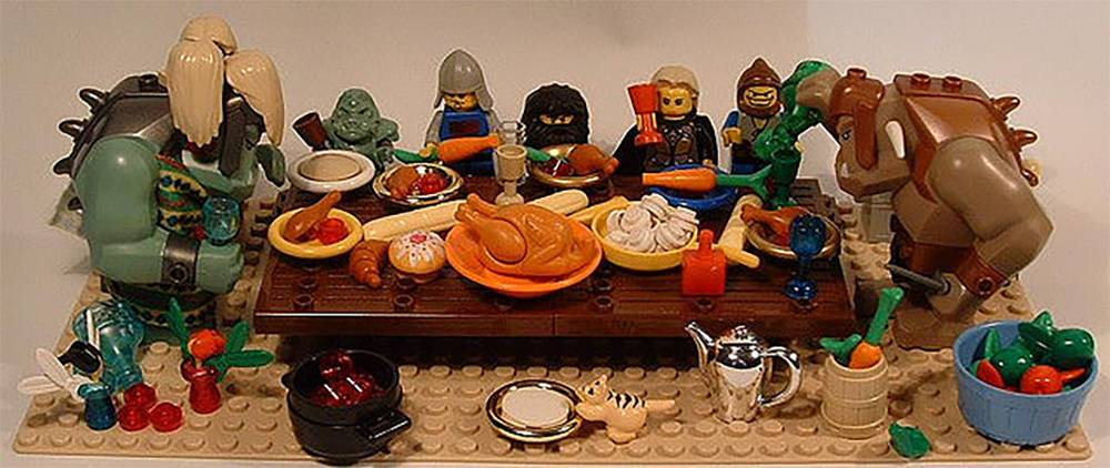 Lego Orcs , goblins, knights, and wizards sit around a thanksgiving table.