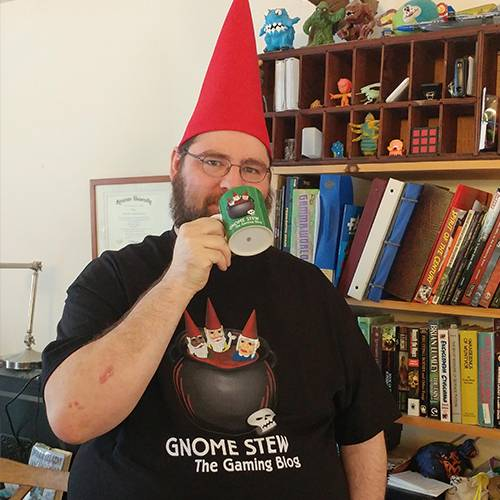 A man with a red gnome hat, a green Gnome Stew Mug raised to his lips, and wearing a black Gnome Stew t-shirt.