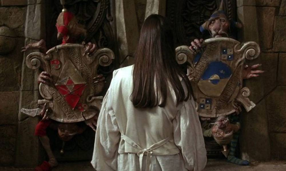 Sarah (tall, dark brunette hair) from the movie Labyrinth stands in front of two door muppets with shields. They are old and strange creatures, with scaly hands (4 each) and legs.Their faces look like a hairless dog of cat, and they each have shields. One has red adornments, the other is blue.
