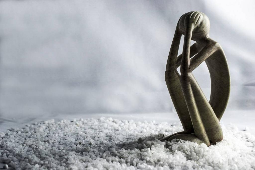 A wooden figurine, skinny with long legs, hunches in on itself with hands on its head. It evokes a feeling of sadness and contemplation. There is salt on the ground and a white background, giving a stark and snowy feeling agaisnt the light tan wood with the multiple bands of thin darker ridges.