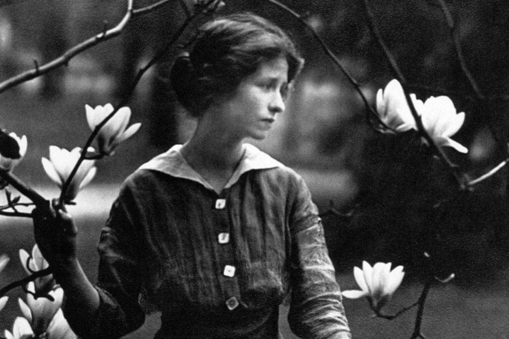 image of poet Edna St. Vincent Millay. black and white image of a woman standing and looking to the right with branches of a flowering tree in the foreground