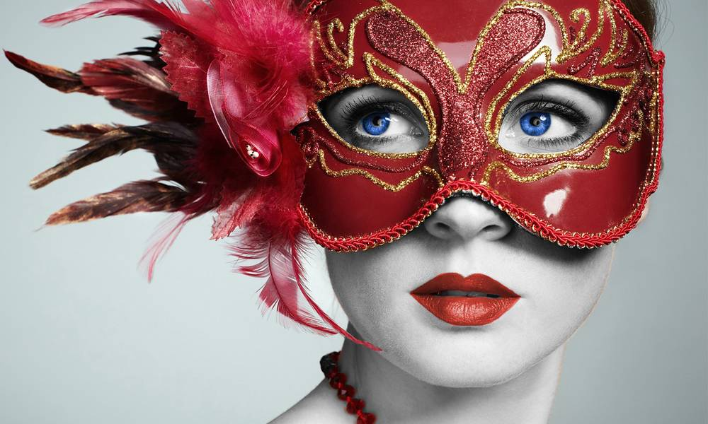 Woman in a red mask with feathers looking away