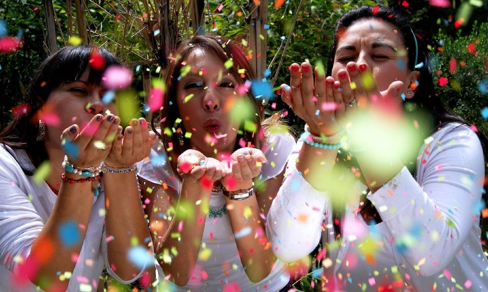 Three women blow confetti at the camera