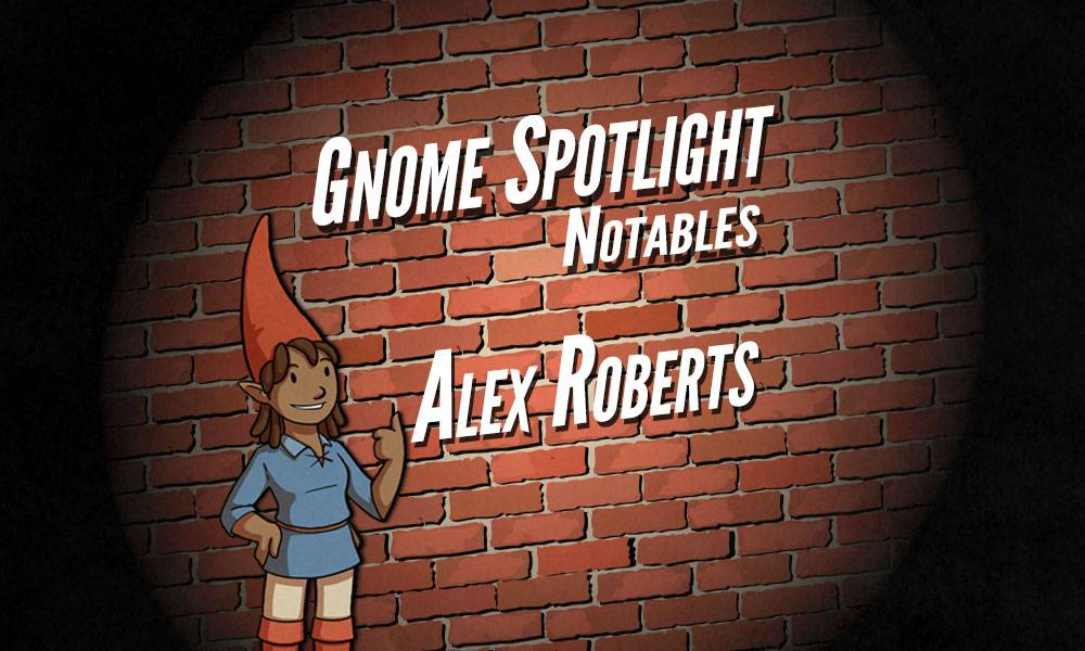 The gnome spotlight header, a daker skinned female gnaome gives a thumbs up in front of a brink wall in a spotlight. The text reads Gnome Spotlight Notables - Alex Roberts