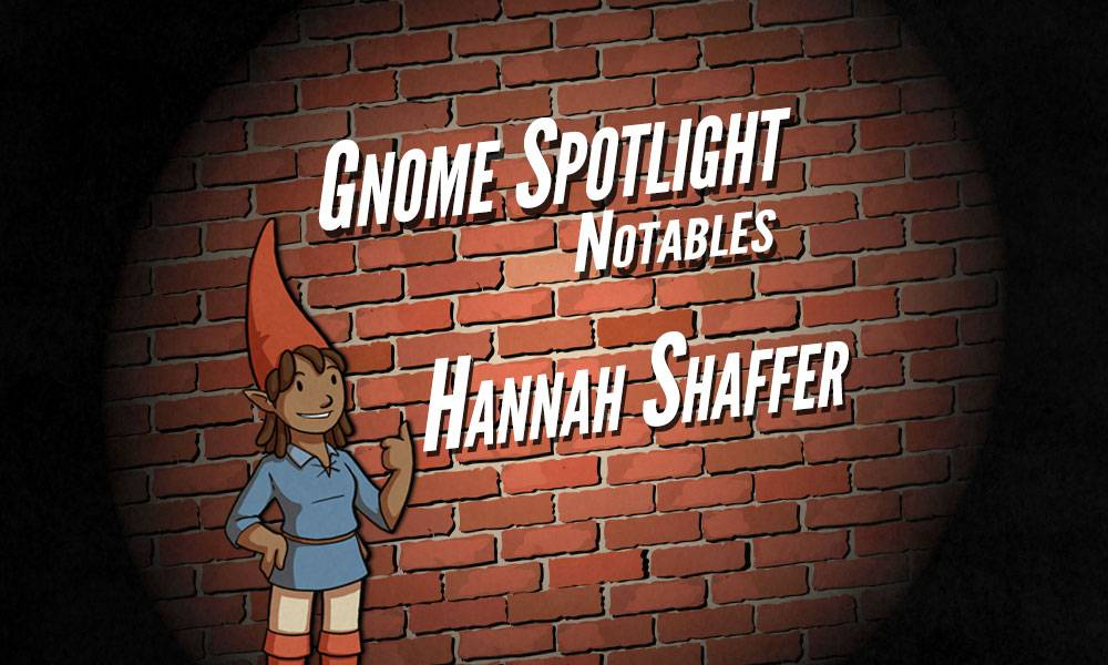 The gnome spotlight header, a daker skinned female gnaome gives a thumbs up in front of a brink wall in a spotlight. The text reads Gnome Spotlight Notables - Hannah Shaffer