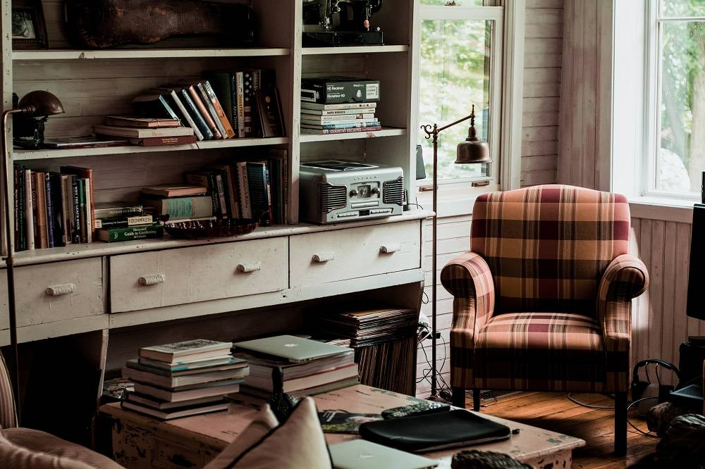 a cozy reading room with natural lighting, a plaid armchair, and stacks of books