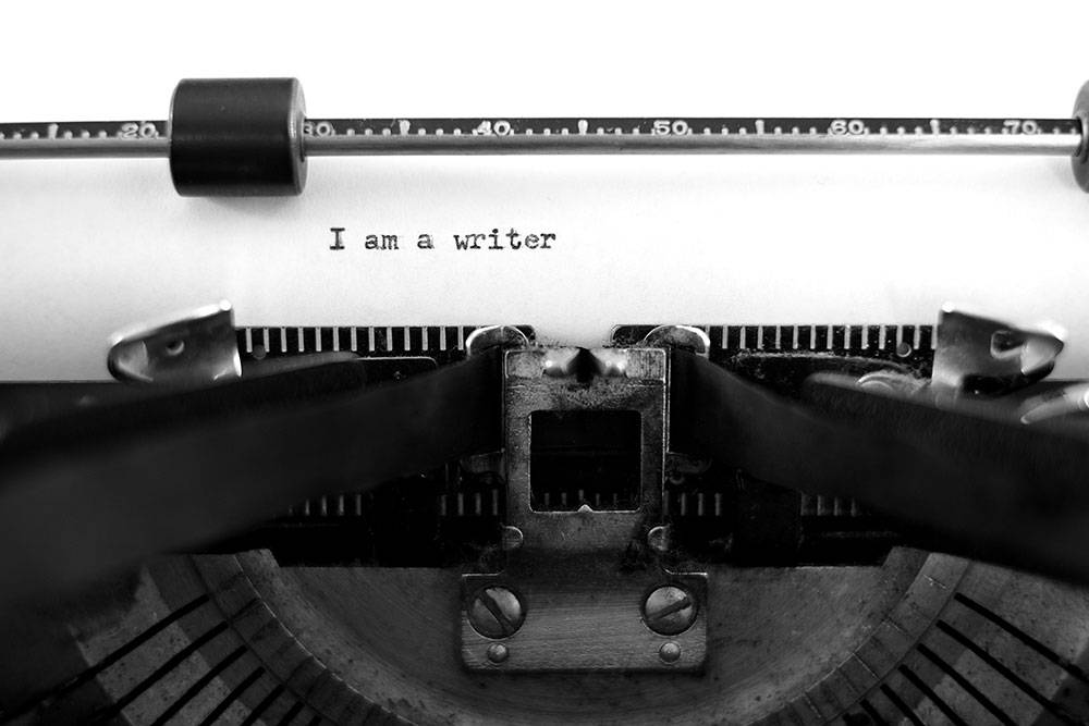 "An old black and white photo of a typewriter, the text "" I AM A WRITER"" is on the page, but otherwise it is blank."