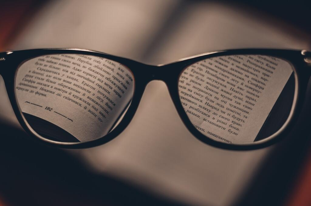A book that is fuzzy and barely visible, but there are glasses in front of the viewer that clear up the image and show some words and page numbers.