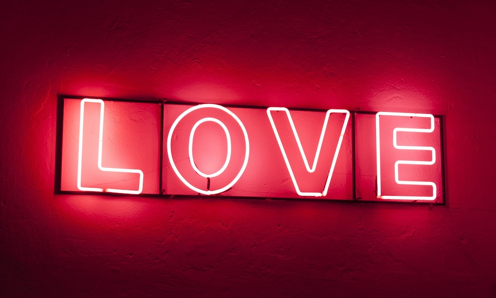 """Love"" in red neon letters on a red wall"