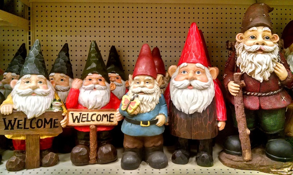 A shelf of garden gnomes, many of them holding welcome signs