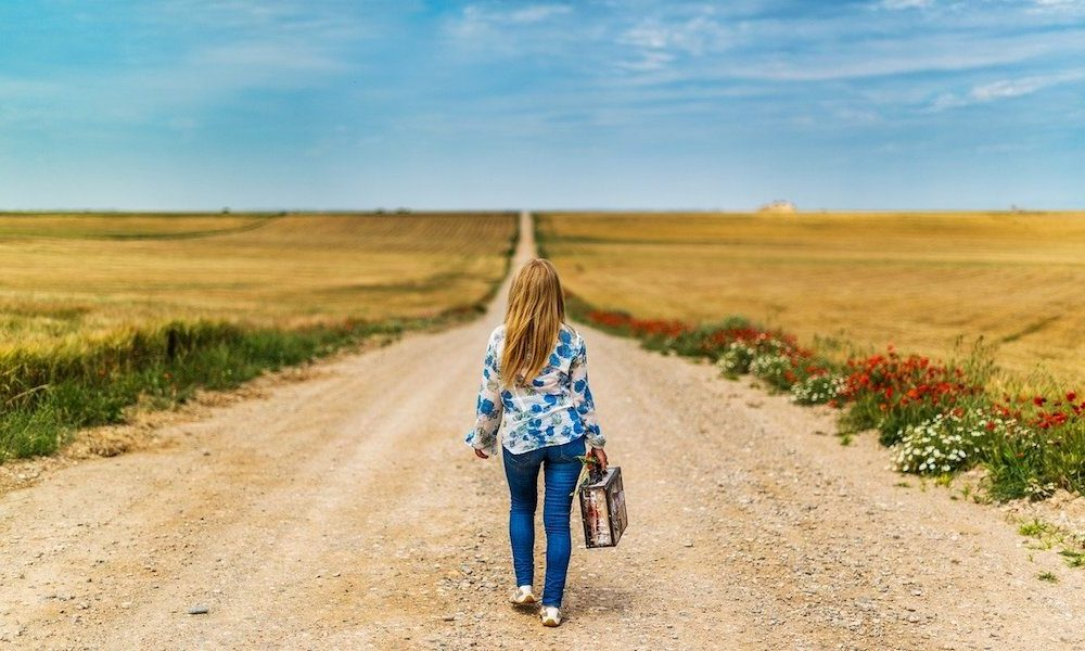 a girl walks down a dirt road with a suitcase with her back to the camera