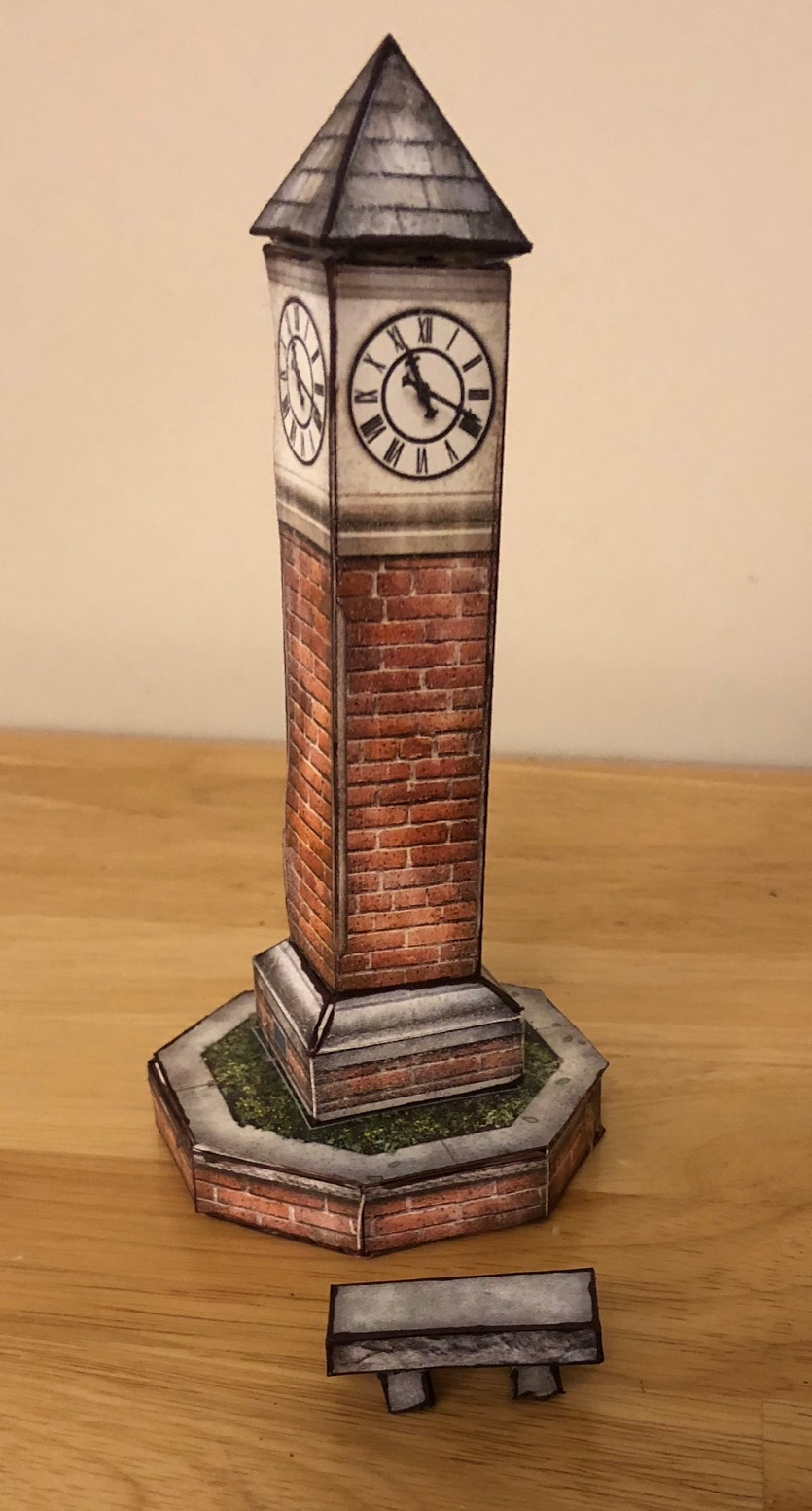 A papercraft clock tower and bench with stone texture.