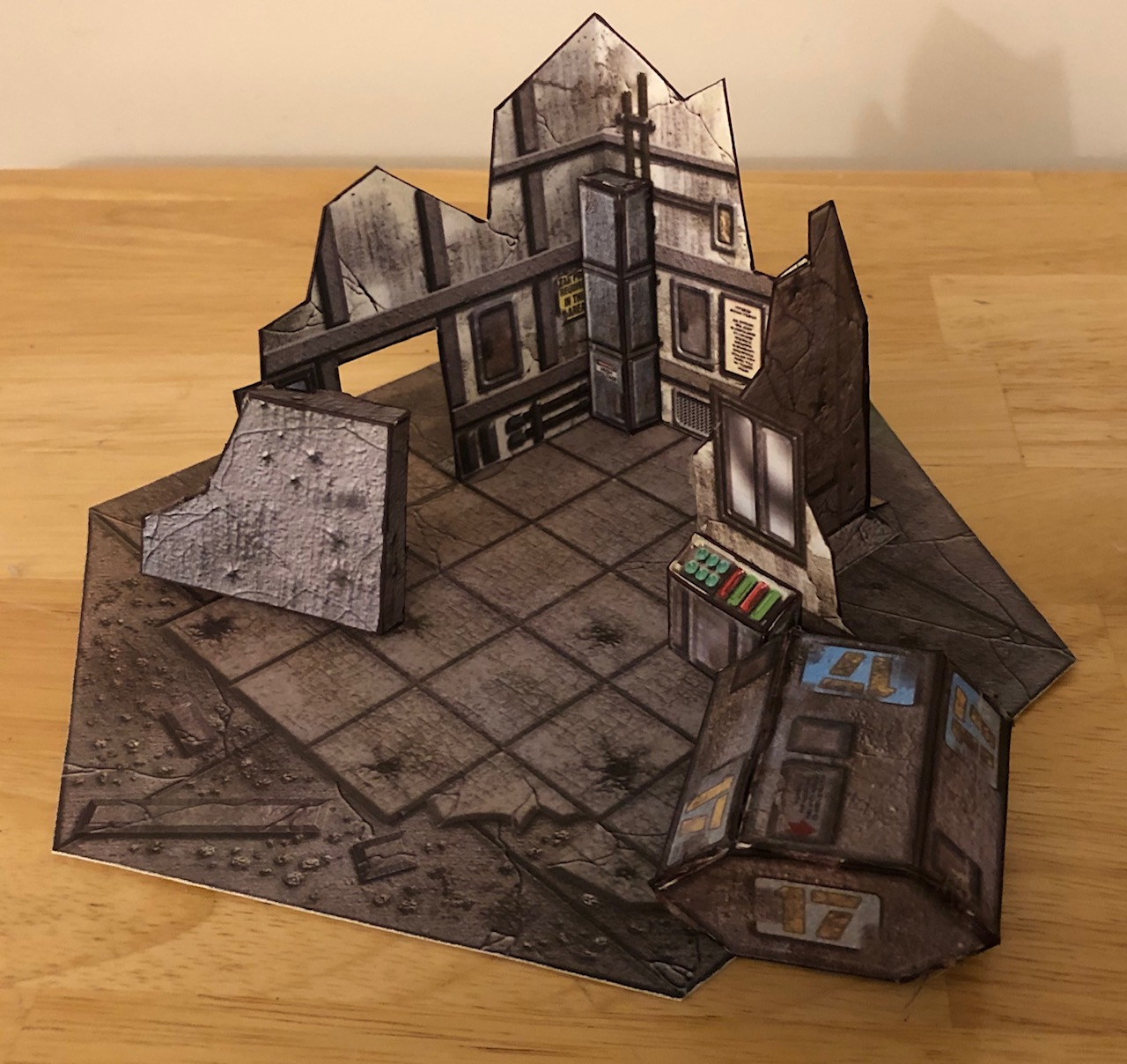A papercraft industrial building, wrecked, along with some scatter pieces, also papercraft.