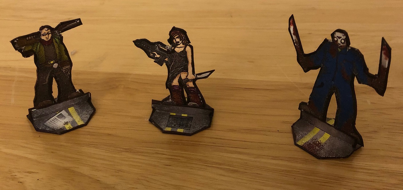 Three papercraft miniatures: an old man with a shotgun, a young woman with a gun and knife, and a masked villain with machetes.