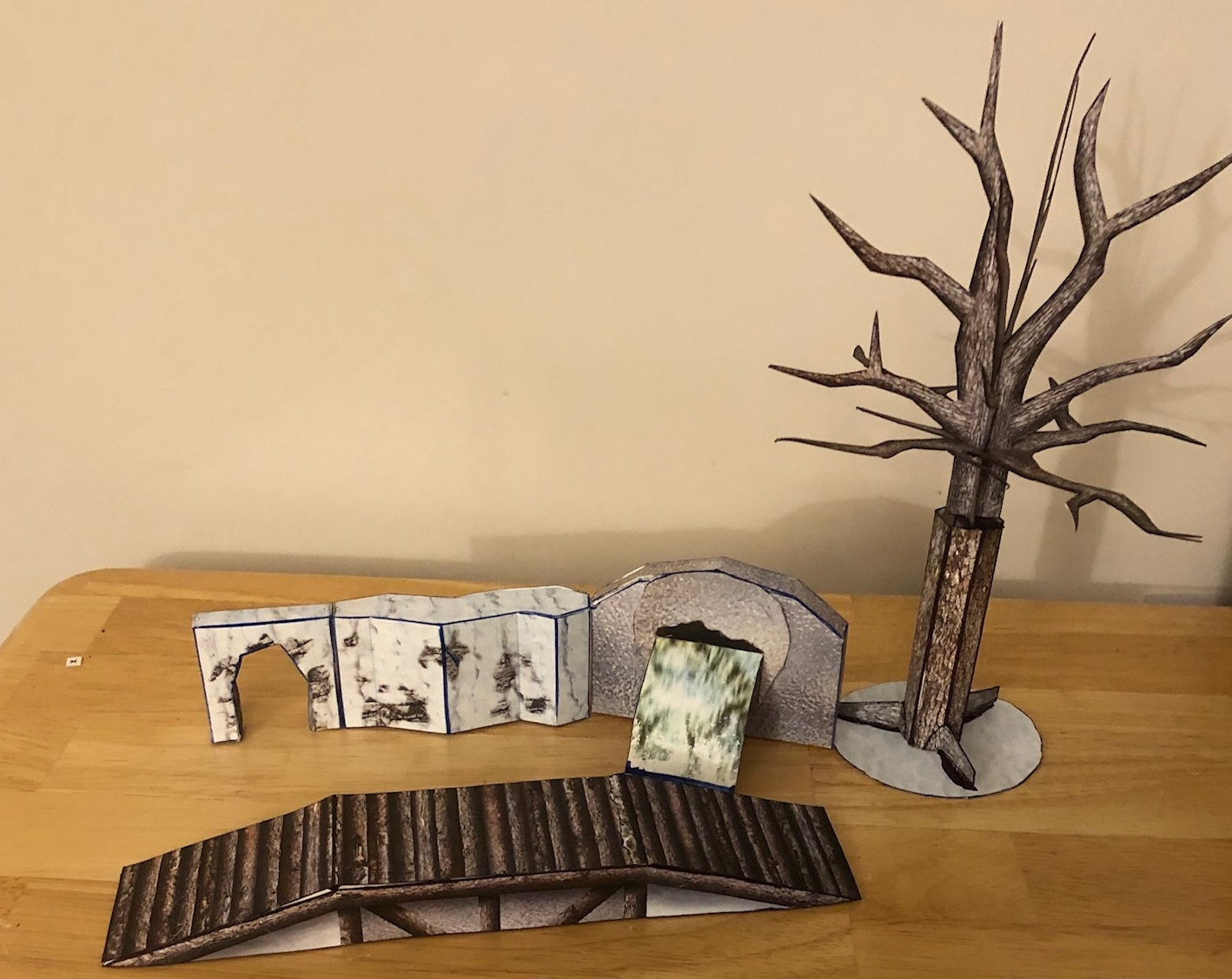 An ice cave wall, ice cave entrance, frozen waterfall, and bare tree all made from papercraft.