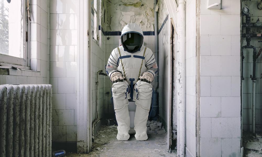 An astronaut sits on a toilet in a run down white tiled bathroom