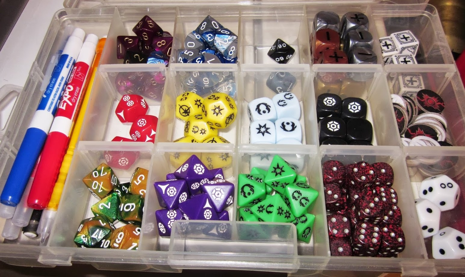 A plastic toolbox full of dice, tokens, and markers.