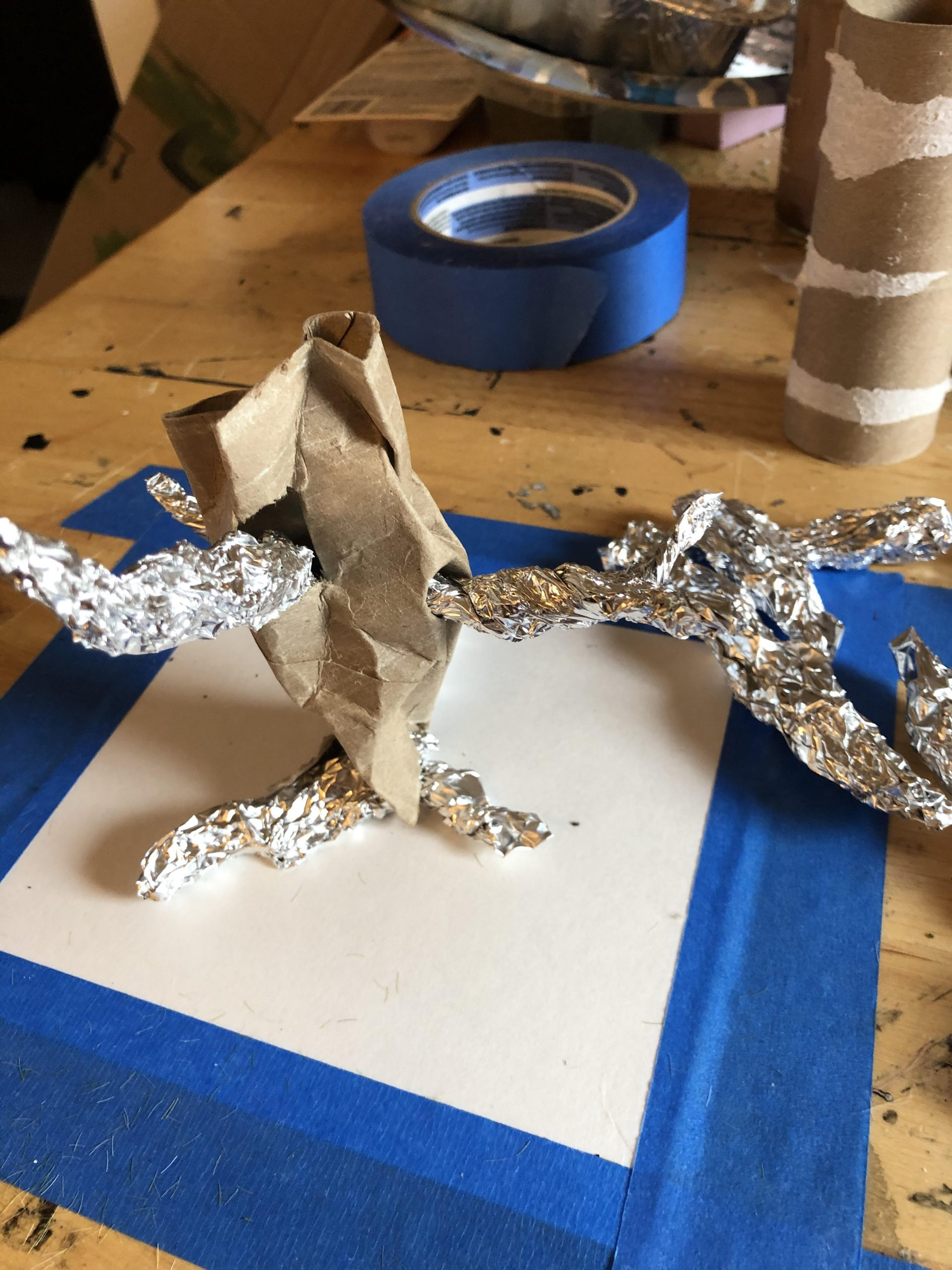 A toilet paper roll and aluminum foil, shaped into something roughly approximating the shape of a tree trunk.