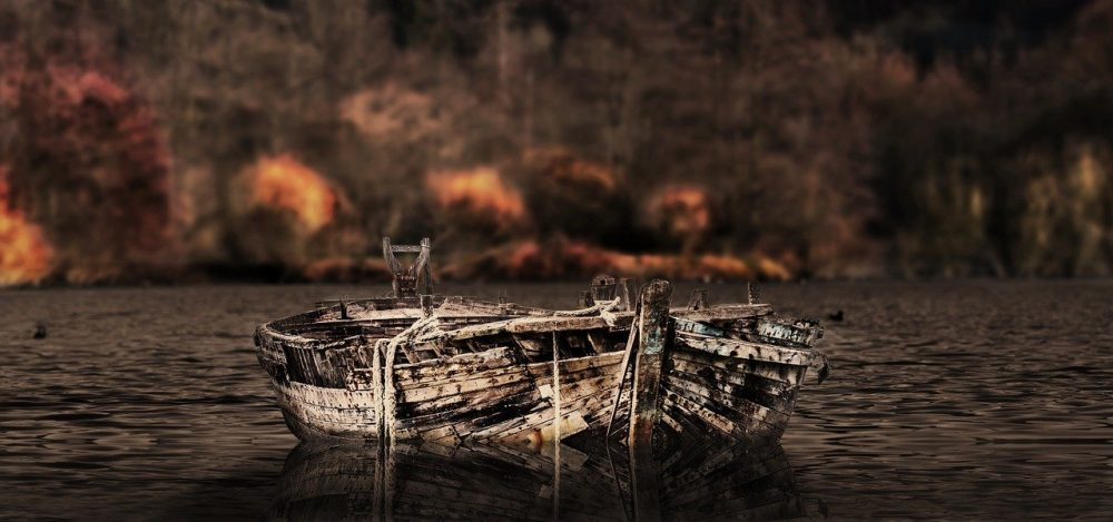 A decaying boat sitting in the middle of a lake