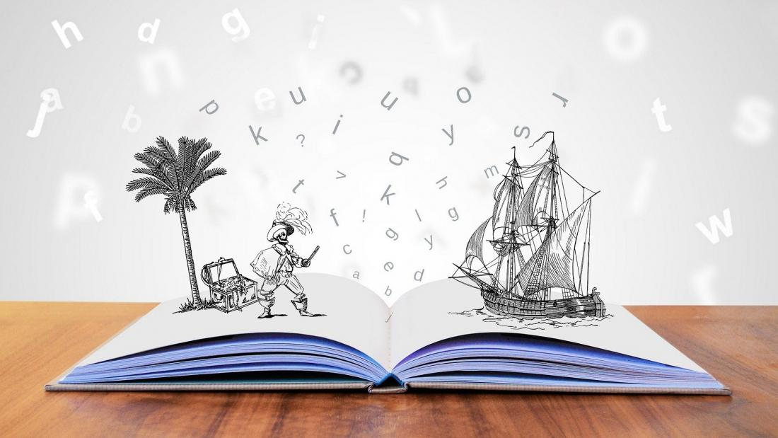 An open book on a table with an image of a pirate standing on one side and a ship on the water on the other.