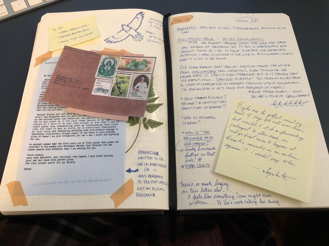 open pages of a journal with a letter and envelope, notes, and stickies