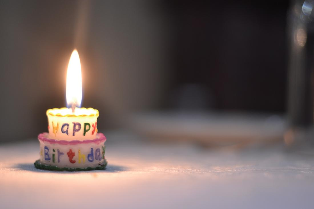 Small birthday cake with a single candle sitting on a table.
