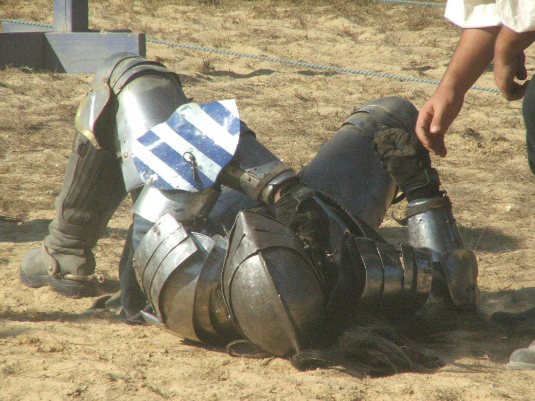 Photograph of a knight lying on their back on the ground, looking defeated.