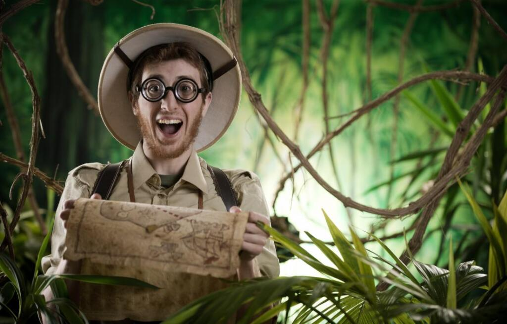 A white male excitedly looks into the camera. He's wearing an stereotypical explorer's outfit, and holds a parchment map. Behind him is a jungle.xplorer's